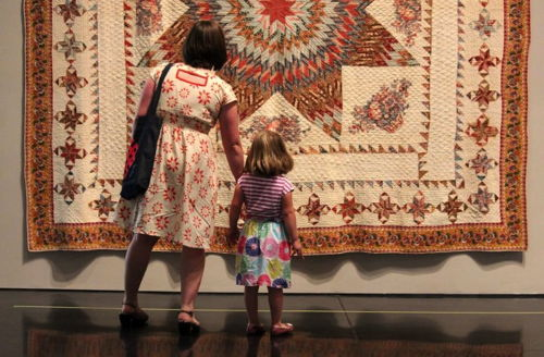 Mother and daughter admiring a quilt